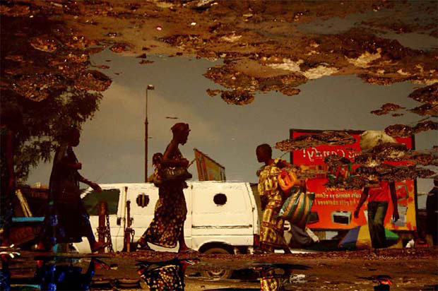 Surreal Photos of Daily Life in Kinshasa Taken Through Trash-Strewn Puddles