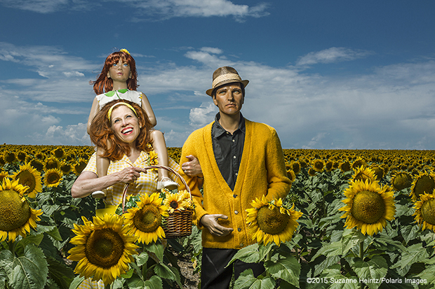 """Aug 16, 2015 - Denver, CO: Conceptual Photographer, Suzanne Heintz, beams with pride beside her imitation husband and daughter in an American Pasture. Part of her 14 year self-portrait photo series, LIFE ONCE REMOVED, in which Heintz satirizes the image of a """"Perfect Life."""" She uses humor to comment on mid-20th Century societal expectations still present for women of a """"Certain Age"""" to marry and have children. She recreates all aspects of family life with her store bought family, featuring them in scenes of blissful domestic life in and outside of the home, traditional holidays, and idyllic family vacations. (Suzanne Heintz / Polaris)"""