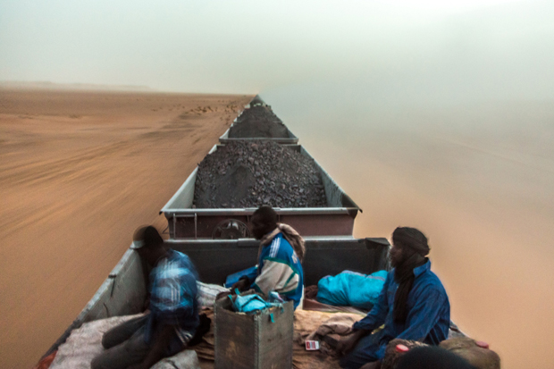 One is free to travel on top of the iron ore train that crosses the Sahara desert from the mine at Zouérat, in northern Mauritania, to Nouadhibou harbor, on the Atlantic coast of West Africa, as seen on 1st of September 2015. The travelers, usually traders that transport food and live animals, have to endure strong winds and temperatures that can reach 50 degrees Celsius in the summer, during the 20-hour trip.