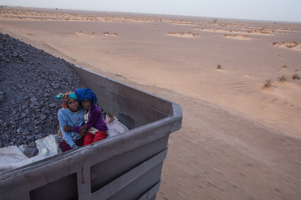 Two minor sisters pose for a portrait while traveling with their family (not seen) on the train loaded with iron ore that crosses the Sahara desert from the mine at Zouérat, in northern Mauritania, to the Nouadhibou harbor, on the Atlantic coast of West Africa, as seen on 1st of October 2015.