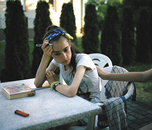 Ania sits outside and writes in her journal. She misses everyone back home.