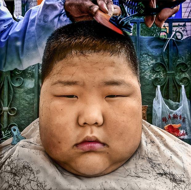 CHINA. Dalian. 2010. A boy gets a haircut in the street.