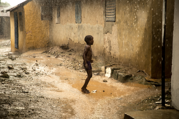 Boy under the rain in the street of Cap Skyrring, Senegal.