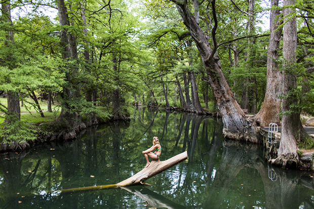 A young woman enjoys a calm swimming hole, the Blue Hole, near Wimberley, Texas.
