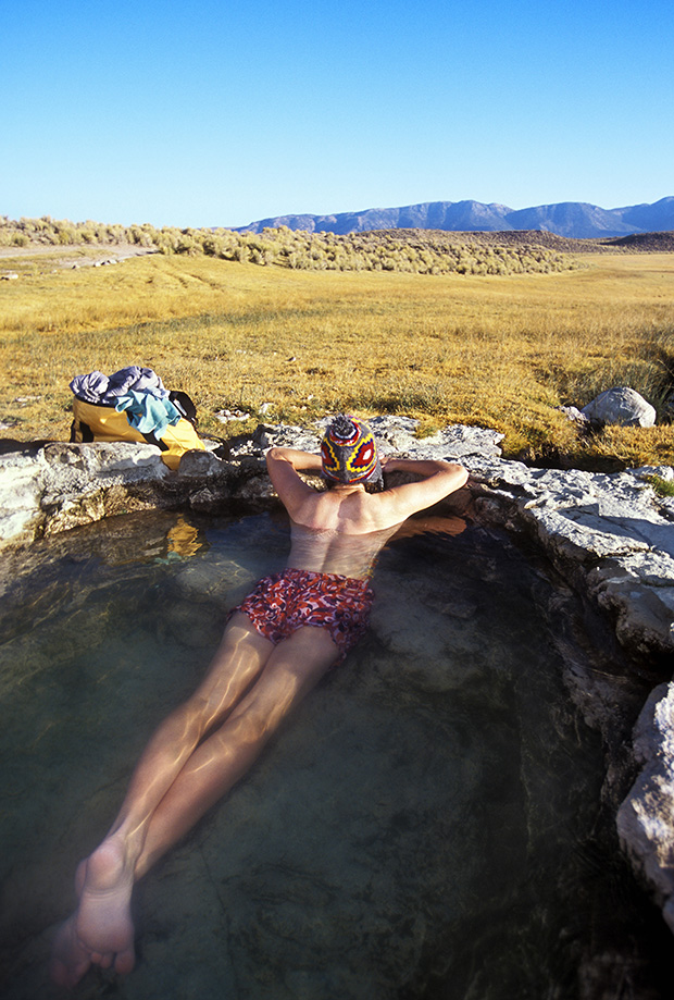 Lone woman sitting in hotspring in California.