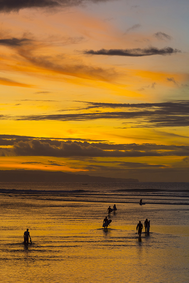 Surfers at sunrise. Bali. Indonesia.