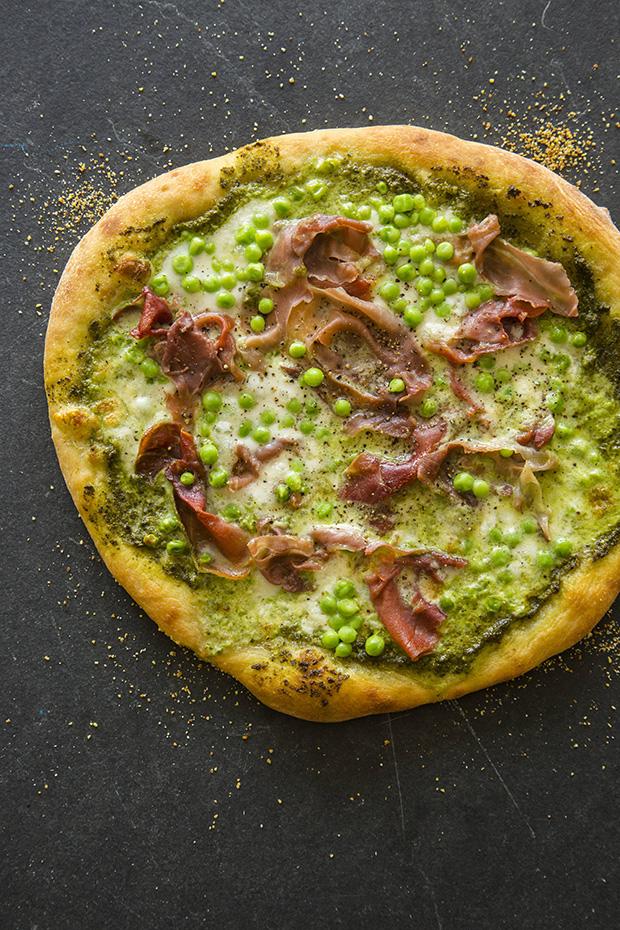 English pea, proscuitto and burrata pizza with pesto sauce.