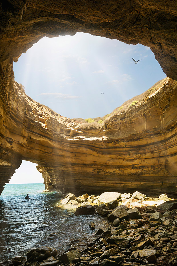A swimmer wades in the water of a sea cave in Sunset Cliffs in San Diego, California.