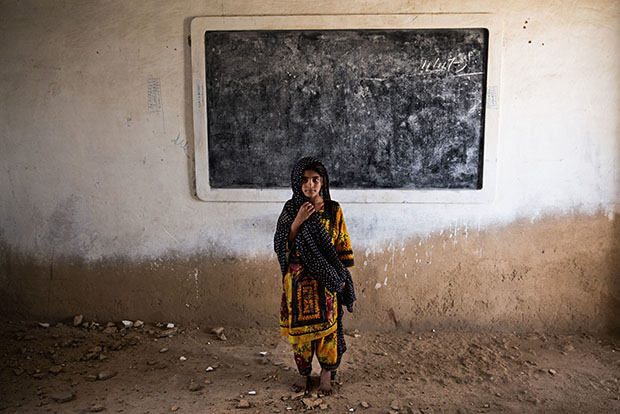 14. Six year old Gul Bano stands in the ruins of her classroom i