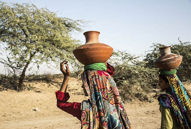 20. Women collect water in traditional terracotta pots from the