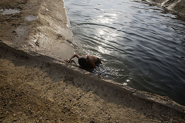 28. A boy climbs out of the canal after a swim in Noor Muhammad