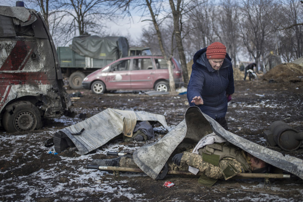 The battle for strategically important railway junction Debaltsevo was one of the fiercest of the entire war in Eastern Ukraine and resulted in a defeat for the Ukrainian army. A resident of Debaltsevo Lyudmila, 66, covers body of the Ukrainian officer. February 20 2015, Ukraine, Debaltsevo. Photographer: Dmitry Beliakov/ for The Sunday Times