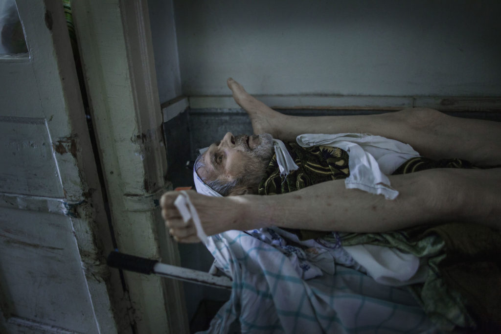 In a Donetsk morgue lie two neighbours, both pensioners, killed by artillery strike as they were collecting relief aid, January 31 2015, Eastern Ukraine Photographer: Dmitri Beliakov/ for Russian Reporter Magazine