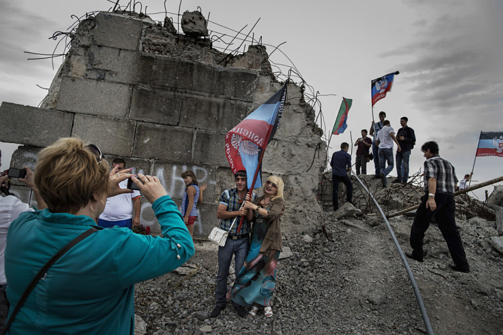 """Remarkable & immediate addiction to the Soviet traditions and celebrations in Soviet style has stricken Donetsk People Republic. DNR activists seen making selfie at the ruin of WW II war memorial, heavily destroyed one year ago at the time of the intensive fighting between the Ukrainian army and the Russian-backed separatists. The Soviet-style decorated official celebrations in anniversary of """"2nd liberation of Donbas from the fascists"""" were organized to seal the victory of the Russian-backed separatists over Ukrainian army, September 7th 2015, Saur-Mohila, Eastern Ukraine Photographer: Dmitri Beliakov/ for Stern"""