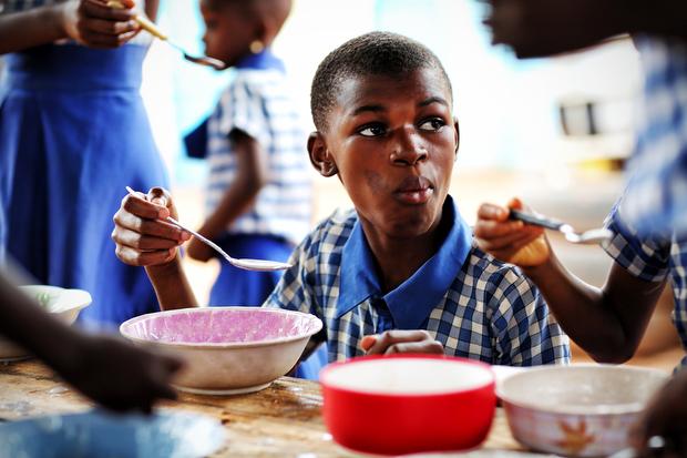 Patience enjoys her morning porridge at school.