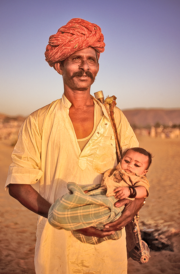 Chitter Bhopa, a Bhopa-bhopi singer-priest, holding baby, Pushkar Fair, Pushkar, Rajasthan, India